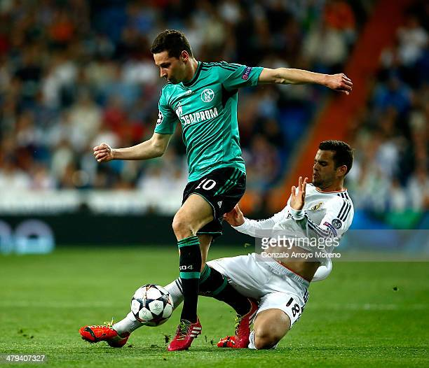Julian Draxler of Schalke is tackled by Nacho Fernandez of Real Madrid during the UEFA Champions League Round of 16 second leg match between Real...