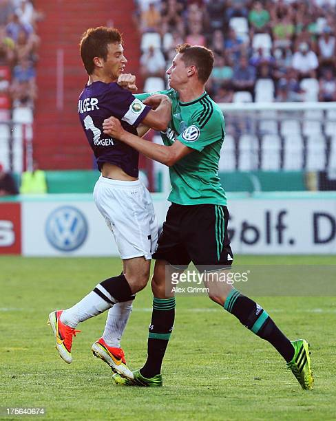 Julian Draxler of Schalke pushes Mario Bilger of Noettingen during the DFB Cup first round match between FC Noettingen and Schalke 04 at...