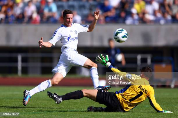Julian Draxler of Schalke scores the third goal against Enver Marina of Saarbruecken during the first round DFB Cup match between 1 FC Saarbruecken...