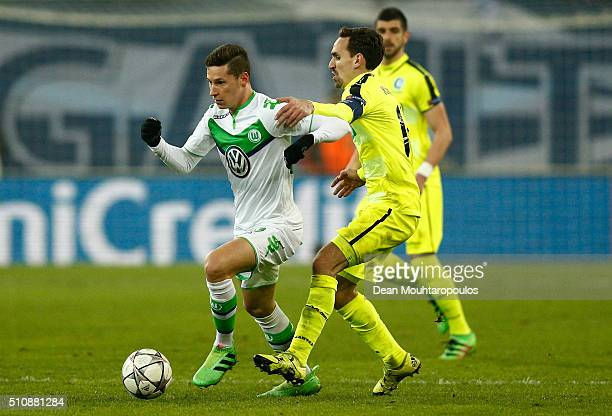 Julian Draxler of Wolfsburg is challenged by Sven Kums of KAA Gent during the UEFA Champions League round of 16 first leg match between KAA Gent and...