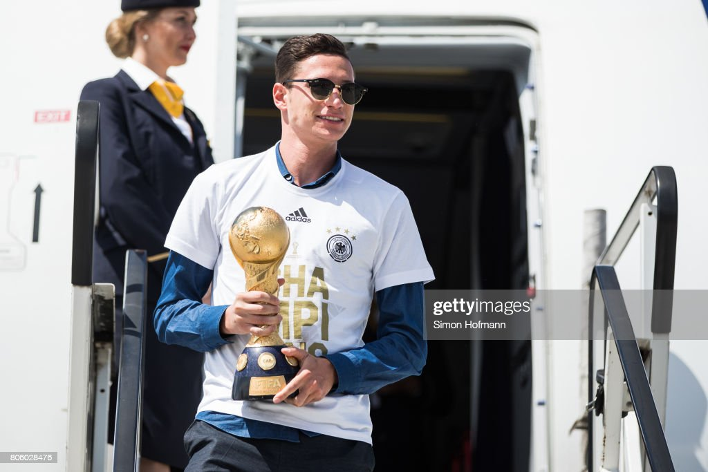 Julian Draxler presents the trophy as he departs the plane carrying the Germany National Football Team during the arrival at Frankfurt International Airport on July 3, 2017 in Frankfurt am Main, Germany.