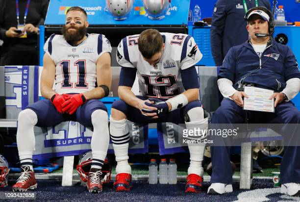 Julian Edelman and Tom Brady of the New England Patriots sit on the bench with offensive coordinator Josh McDaniels prior to Super Bowl LIII against...