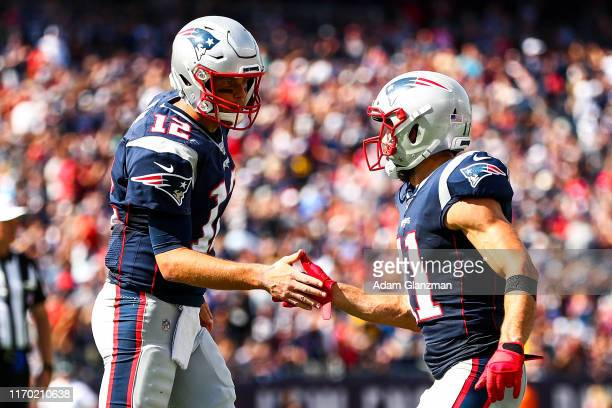 Julian Edelman high fives Tom Brady of the New England Patriots after a touchdown in the second quarter of a game against the New York Jets at...