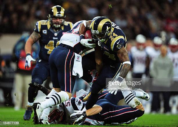 Julian Edelman of the New England Patriots and Jeff Tarpinian of the New England Patriots tackle Isaiah Pead of the St Louis Rams during the NFL...