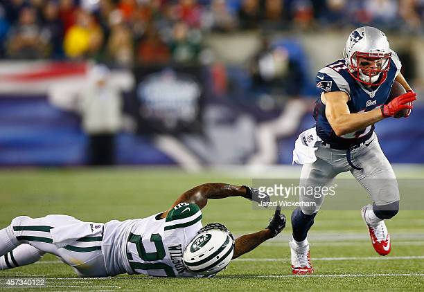 Julian Edelman of the New England Patriots avoids a tackle by Kyle Wilson of the New York Jets during the fourth quarter at Gillette Stadium on...