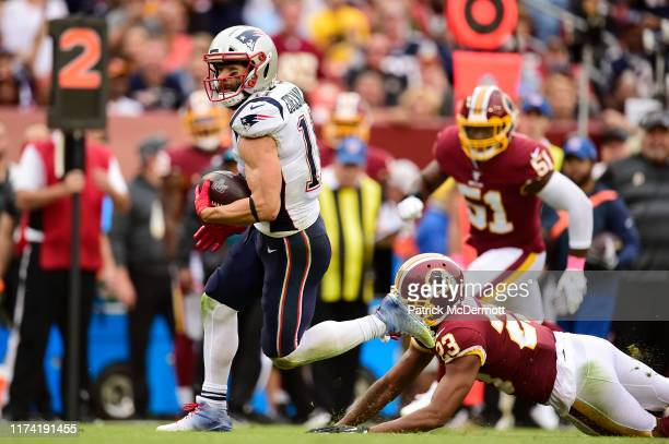 Julian Edelman of the New England Patriots avoids the tackle of Quinton Dunbar of the Washington Redskins in the third quarter at FedExField on...