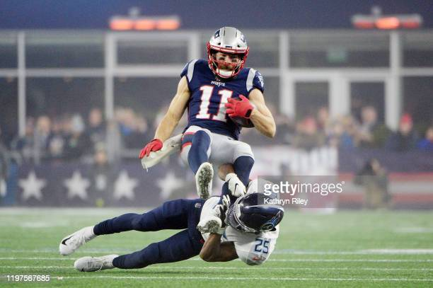 Julian Edelman of the New England Patriots carries the ball against Adoree' Jackson of the Tennessee Titans in the second quarter of the AFC Wild...
