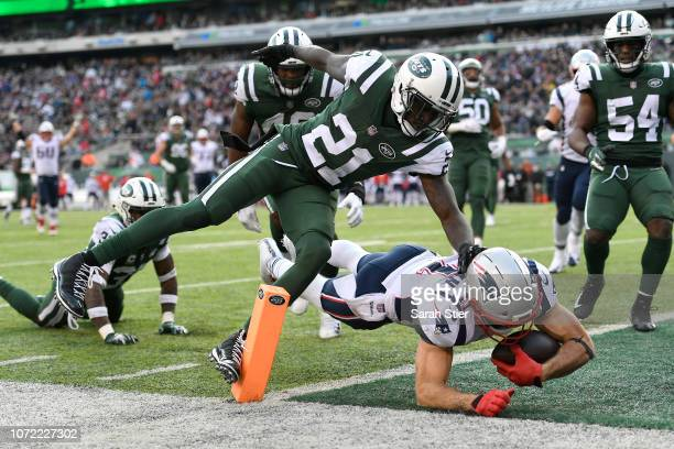 Julian Edelman of the New England Patriots dives into the end zone for a third quarter touchdown past Morris Claiborne of the New York Jets at...