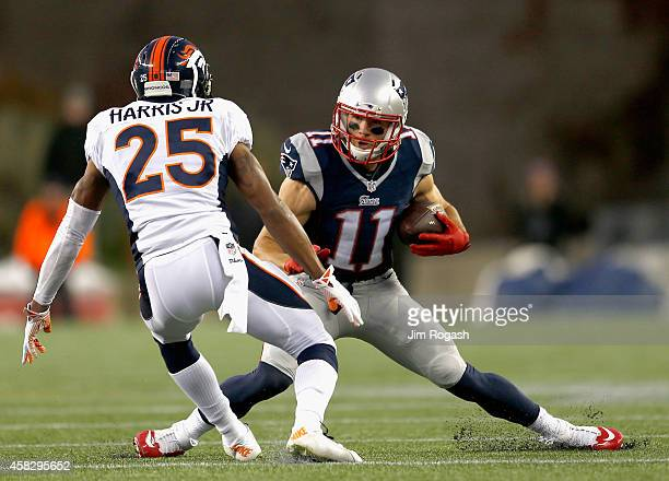 Julian Edelman of the New England Patriots evades a tackle by Chris Harris Jr #25 of the Denver Broncos during the first quarter at Gillette Stadium...