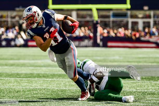Julian Edelman of the New England Patriots evades a tackle by Jamal Adams of the New York Jets during the second quarter of a game at Gillette...