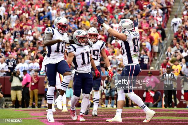 Julian Edelman of the New England Patriots is congratulated by his teammates Josh Gordon Ryan Izzo and Matt LaCosse after scoring a first quarter...