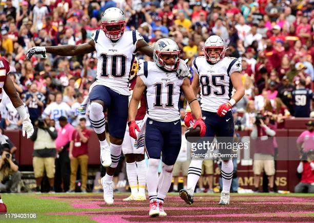 Julian Edelman of the New England Patriots is congratulated by his teammates Josh Gordon and Ryan Izzo after scoring a first quarter touchdown...