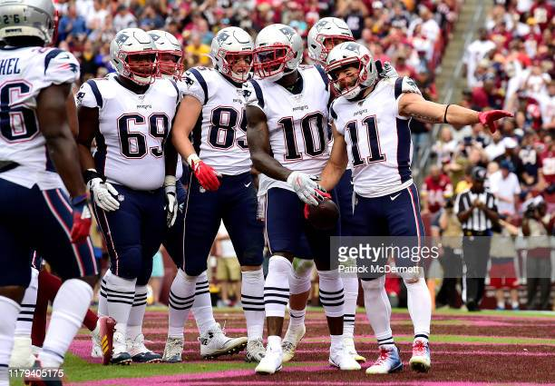 Julian Edelman of the New England Patriots is congratulated by his teammates after scoring a first quarter touchdown against the Washington Redskins...
