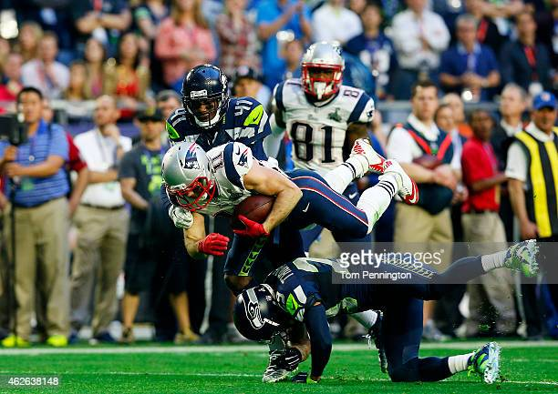 Julian Edelman of the New England Patriots is tacked by Byron Maxwell and Earl Thomas of the Seattle Seahawks in the second quarter during Super Bowl...