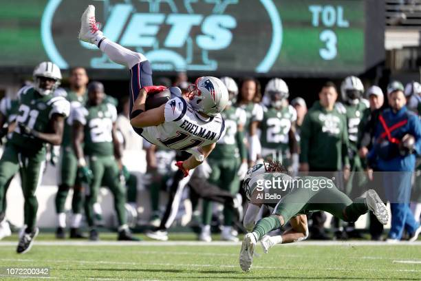 Julian Edelman of the New England Patriots is tackled by Darryl Roberts of the New York Jets after catching a first down reception during the first...