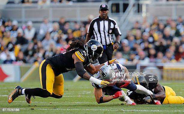 Julian Edelman of the New England Patriots is tackled by Lawrence Timmons and Jarvis Jones of the Pittsburgh Steelers in the first quarter during the...