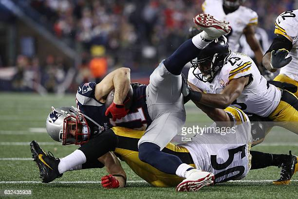 Julian Edelman of the New England Patriots is tackled by Ryan Shazier and Mike Mitchell of the Pittsburgh Steelers in the AFC Championship Game at...