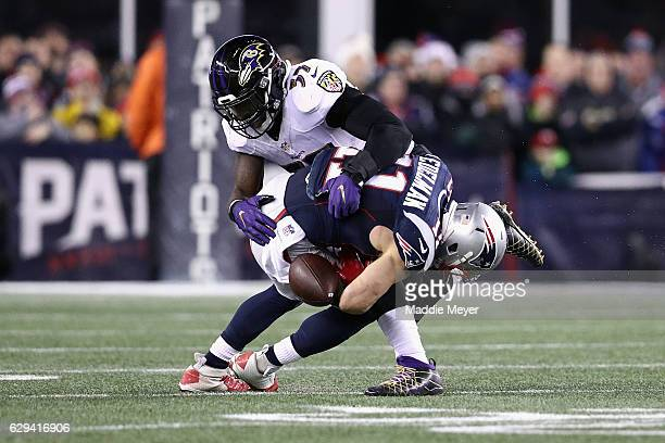 Julian Edelman of the New England Patriots loses control of the ball as he is hit by CJ Mosley of the Baltimore Ravens during the first half of their...