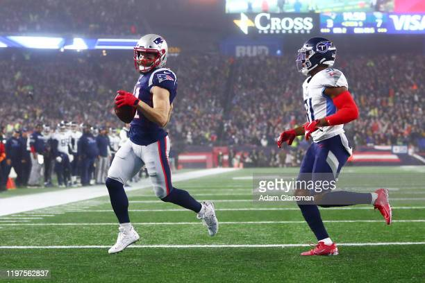 Julian Edelman of the New England Patriots runs in a touchdown against Kevin Byard of the Tennessee Titans in the second quarter of the AFC Wild Card...