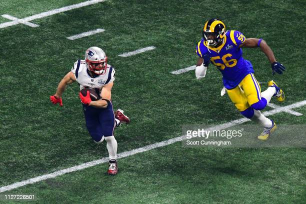 Julian Edelman of the New England Patriots runs the ball against Dante Fowler of the Los Angeles Rams in the second half during Super Bowl LIII at...