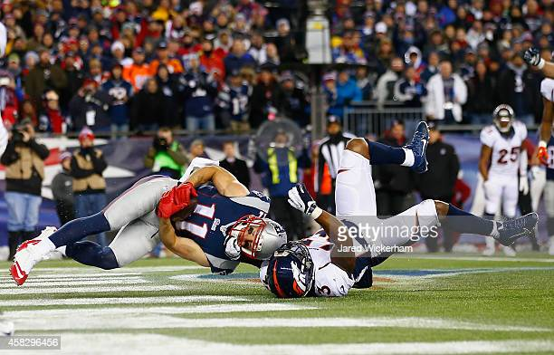 Julian Edelman of the New England Patriots scores a touchdown as he is defended by TJ Ward of the Denver Broncos during the second quarter at...
