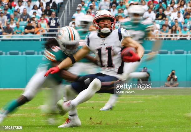 Julian Edelman of the New England Patriots tries to avoid the tackle by Walt Aikens of the Miami Dolphins during the second half at Hard Rock Stadium...