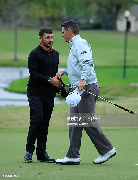 Julian Etulain of Argentina shakes hands with Greg Chalmers of Australia as they finish their round tied for the lead during the third round of the...