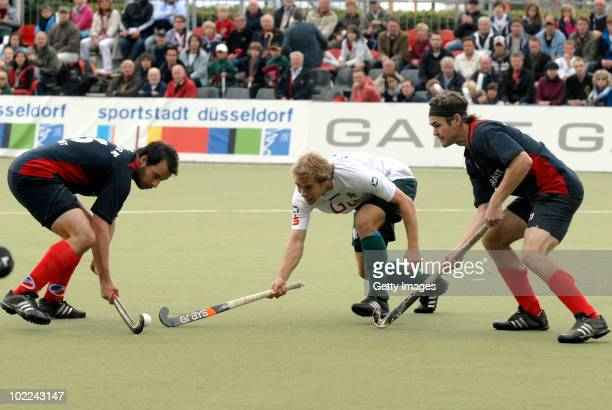 Julian Fischer and Nicolas Emmerling battle for fhe hockey ball with Jan Ruehr of Muehlheim during the men's 3rd/4th place match between Mannheimer...