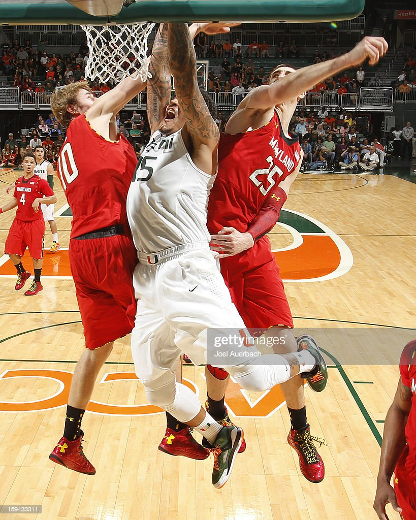 Julian Gamble #45 of the Miami Hurricanes splits the defense of Jake Layman #10 and Alex Len #25 of the Maryland Terrapins to score late in the second half on January 13, 2013 at the BankUnited Center in Coral Gables, Florida. Miami defeated Maryland 54-47.