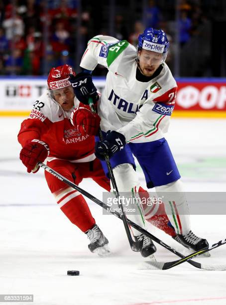 Julian Jakobsen of Denmark challenges Stefano Marchetti of Italy for the puck during the 2017 IIHF Ice Hockey World Championship game between Denmark...