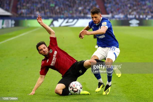 Julian Korb of Hannover 96 is challenged by Alessandro Schoepf of FC Schalke 04 during the Bundesliga match between FC Schalke 04 and Hannover 96 at...
