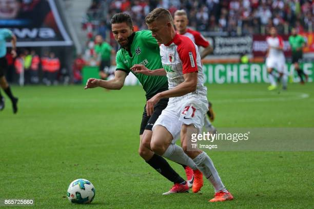 Julian Korb of Hannover and Alfred Finnbogason of Augsburg battle for the ball during the Bundesliga match between FC Augsburg and Hannover 96 at...