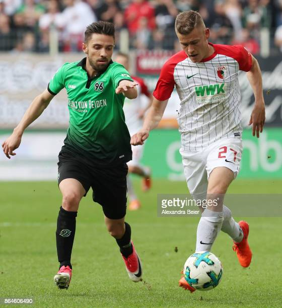 Julian Korb of Hannover and Alfred Finnbogason of Augsburg fight for the ball during the Bundesliga match between FC Augsburg and Hannover 96 at...