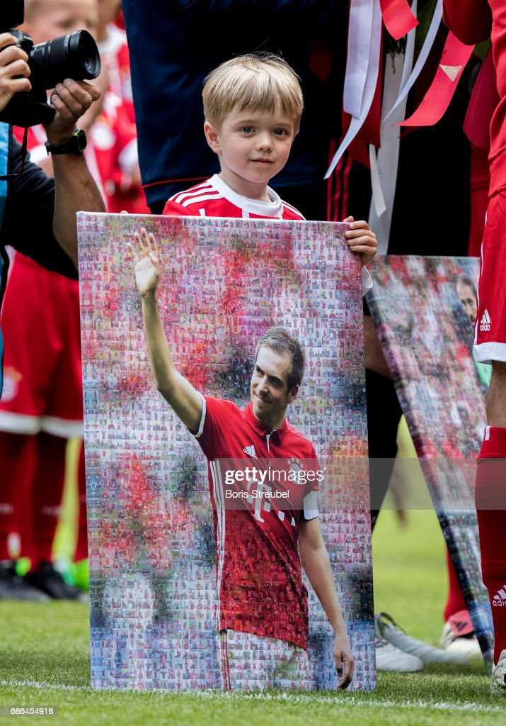 Julian Lahm, the son of Philipp Lahm of FC Bayern Muenchen holds the picture of his father during Phillip Lahm's farewell ceremony ahead of the Bundesliga match between Bayern Muenchen and SC Freiburg at Allianz Arena on May 20, 2017 in Munich, Germany.