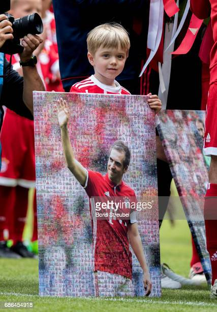Julian Lahm the son of Philipp Lahm of FC Bayern Muenchen holds the picture of his father during Phillip Lahm's farewell ceremony ahead of the...