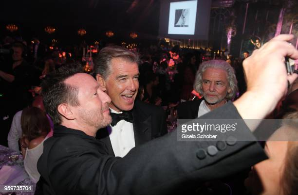 Julian Lennon Pierce Brosnan take a selfie during the amfAR Gala Cannes 2018 dinner at Hotel du CapEdenRoc on May 17 2018 in Cap d'Antibes France