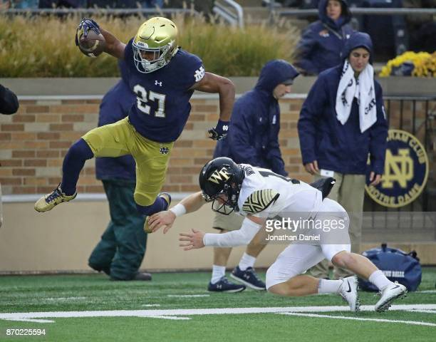 Julian Love of the Notre Dame Fighting Irish is knocked out of bound by John Wolford of the Wake Forest Demon Deacons after an interception at Notre...