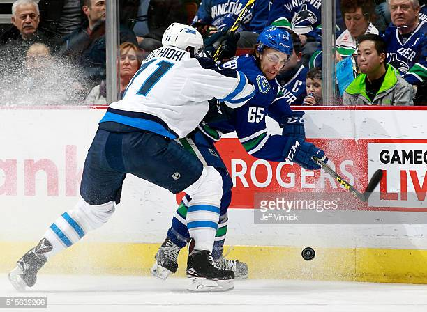 Julian Melchiori of the Winnipeg Jets checks Alexandre Grenier of the Vancouver Canucks during their NHL game at Rogers Arena March 14 2016 in...