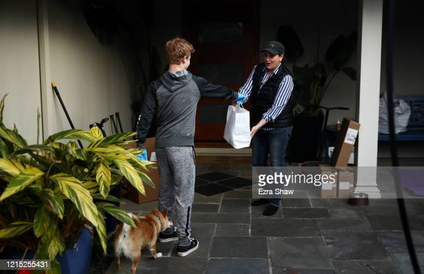 Julian Nichol the son of David Nichol the owner of Sociale delivers a meal to Mary Butler on March 27 2020 in San Francisco California Sociale is...