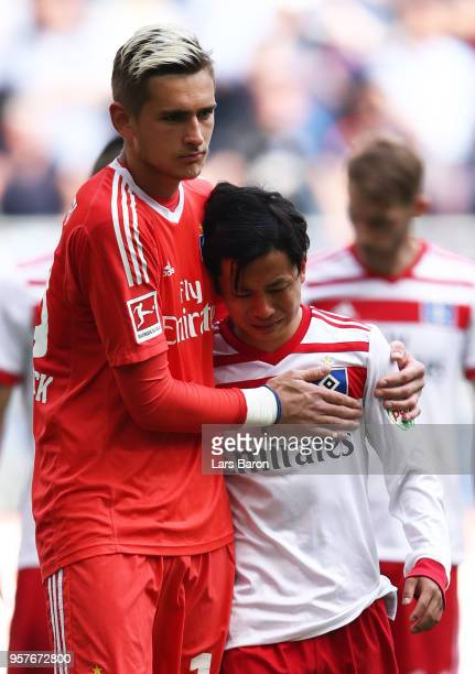 Julian Pollersbeck of Hamburger SV consoles Tatsuya Ito of Hamburger SV as their side are relegated after the Bundesliga match between Hamburger SV...