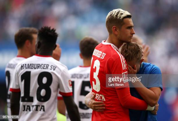 Julian Pollersbeck of Hamburger SV embraces Lewis Holtby of Hamburger SV as they react after their team is relegated after the Bundesliga match...