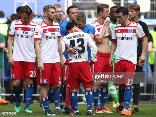 Julian Pollersbeck of Hamburger SV is embraces by Lewis Holtby of Hamburger SV as they react after their team is relegated after the Bundesliga match...