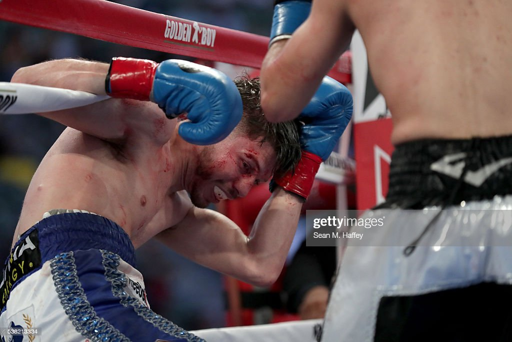 Julian Ramirez (L) falls into the ropes after a punch by Abraham Lopez during their NABA featherweight title at StubHub Center on June 4, 2016 in Carson, California.