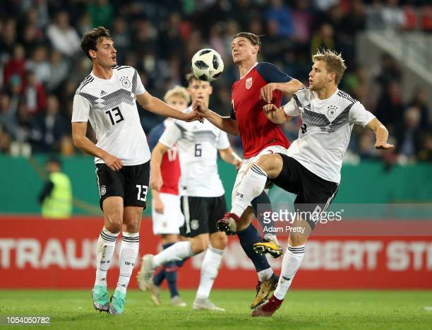 Julian Ryerson of Norway is tackled by Janni Serra and Arne Maier of Germany during the 2019 UEFA Under 21 European Championship Qualifier between...
