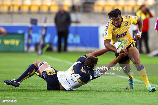 Julian Savea of the Hurricanes beats the tackle of Leon Power of the Brumbies during the round four Super Rugby match between the Hurricanes and the...