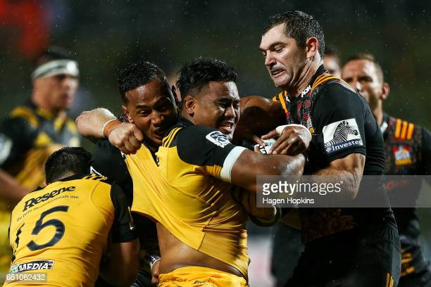 Julian Savea of the Hurricanes is tackled by Toni Pulu and Stephen Donald of the Chiefs during the round three Super Rugby match between the Chiefs...