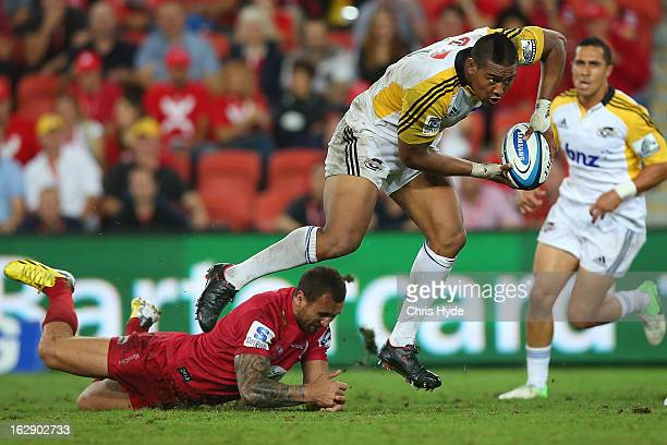 Julian Savea of the Hurricanes makes a run past Quade Cooper of the Reds during the round three Super Rugby match between the Reds and the Hurricanes...