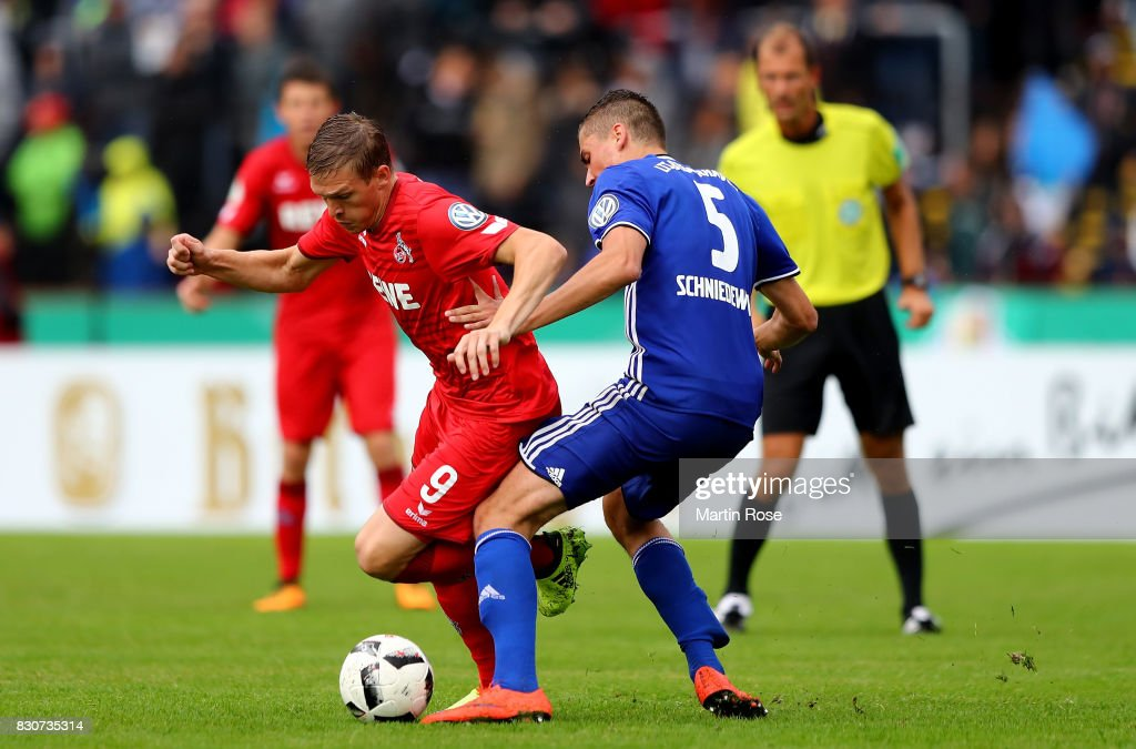 Julian Schniedewind (R) of Leher TS and Artjoms Rudnevs of Koeln battle for the ball during the DFB Cup first round match between Leher TS and 1. FC Koeln at Nordseestadion on August 12, 2017 in Bremerhaven, Germany.
