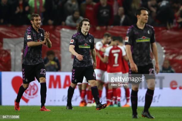 Julian Schuster Caglar Soyuncu and Nicolas Hoefler of Freiburg look dejected after the second Mainz goal during the Bundesliga match between 1 FSV...