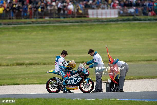 Julian Simon of Spain and Bancaja Aspar Team 125 cc prepares with mechanics in order to celebrate with a mask and flag the victory in 125 cc World...